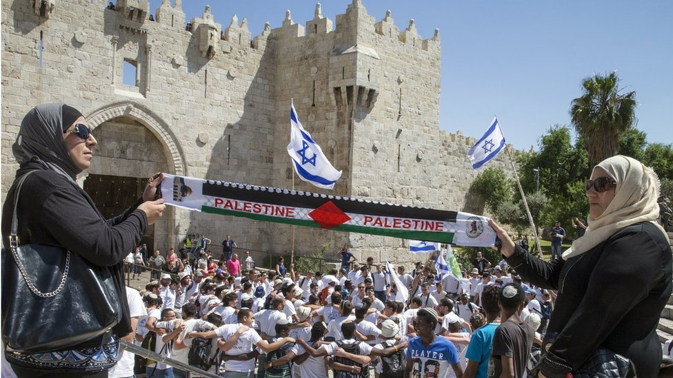 Palestinian women hold 'Palestine' scarf in front of pro-Israel rally in Jerusalem (file photo)