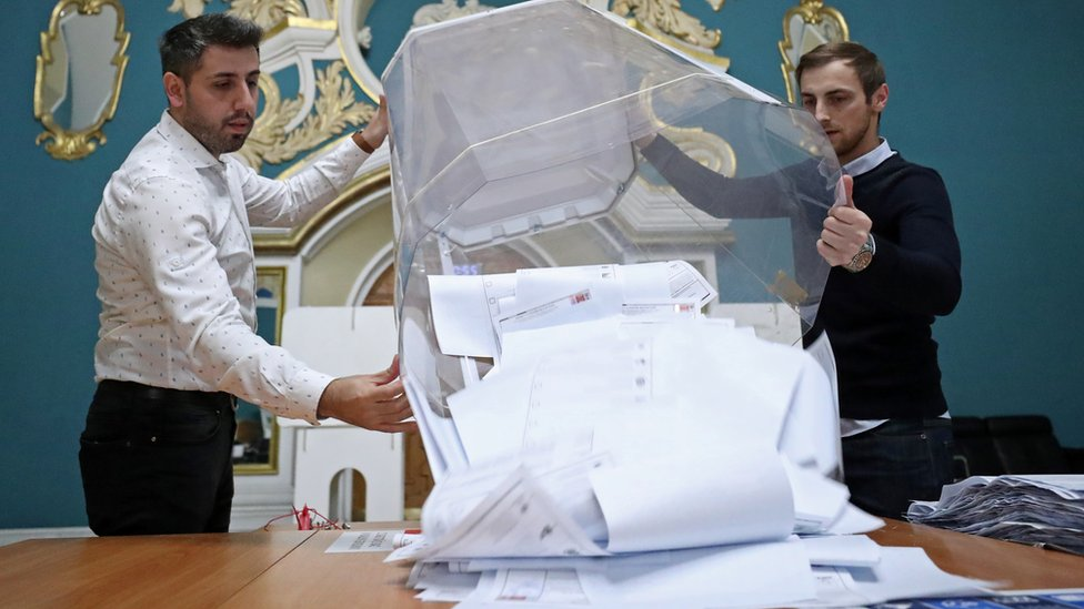 Members of a local election commission empty a ballot box after polls closed during a three-day long parliamentary election, at a polling station inside Kazansky railway terminal in Moscow, Russia September 19, 2021.