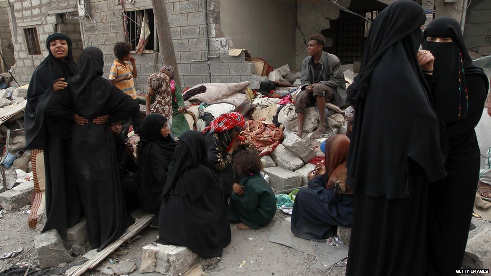 Yemenis gather amid the ruins of a building damaged in an air-strike by the Saudi-led coalition on the capital Sanaa on 13 July, 2015.