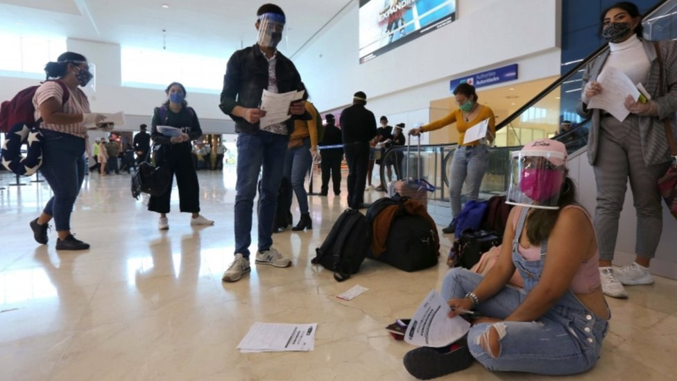 Vários turistas com máscaras em aeroporto