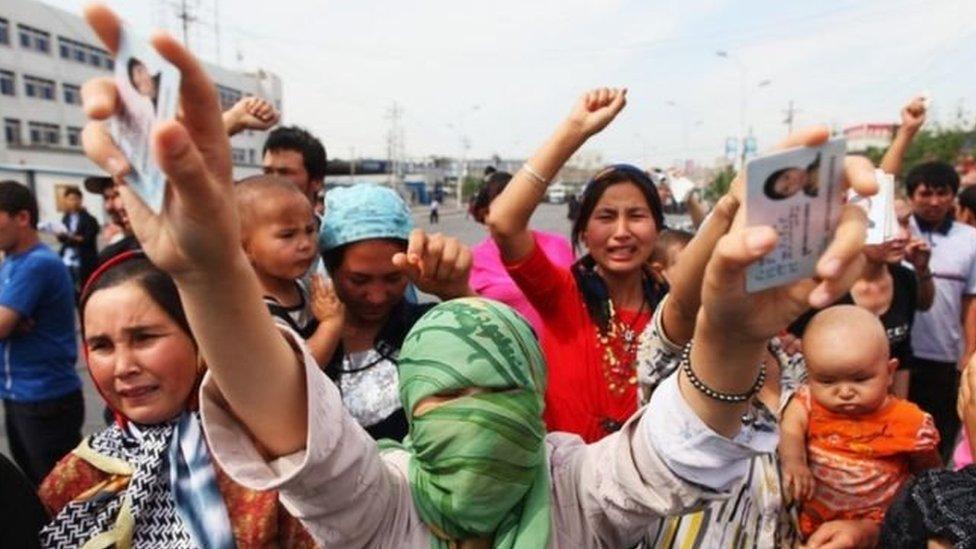 Para pengunjuk rasa Uighur menunjukkan kartu identitas dari kerabat yang ditahan dalam sebuah demonstrasi pada 2009.