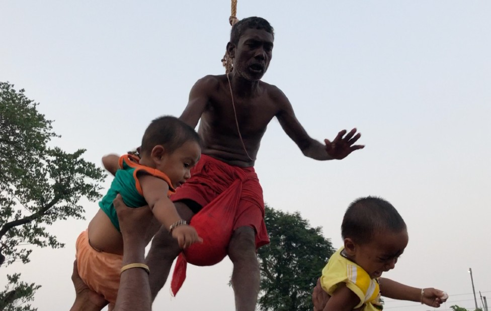 Babies are passed to a devotee suspended by his back