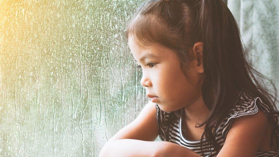 طفلة حزينة تتطلع إلى المطر عبر نافذة