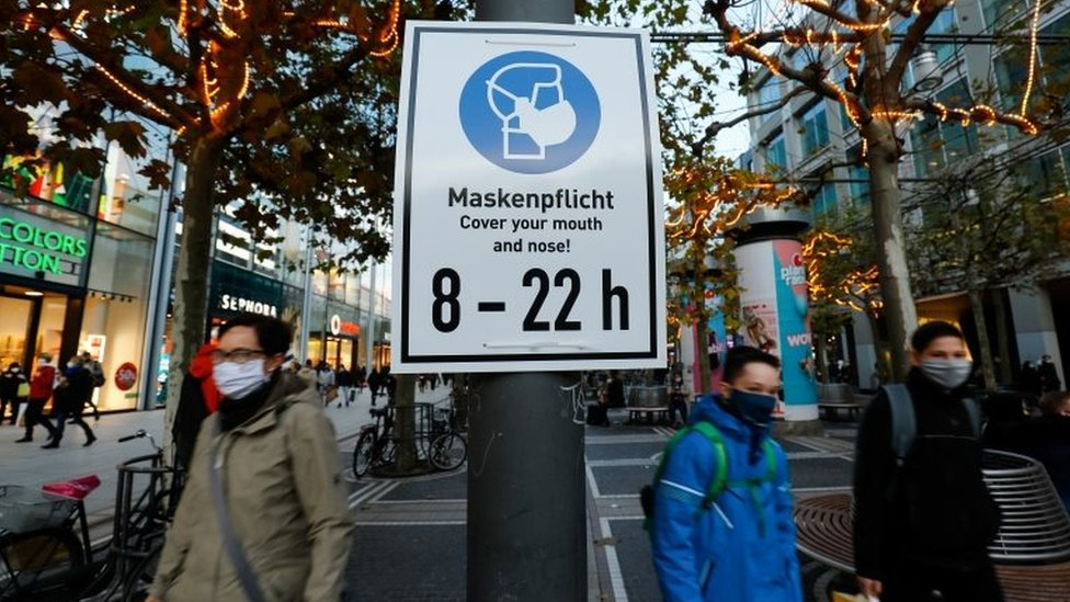 People walk past a sign reminding them to wear a face mask