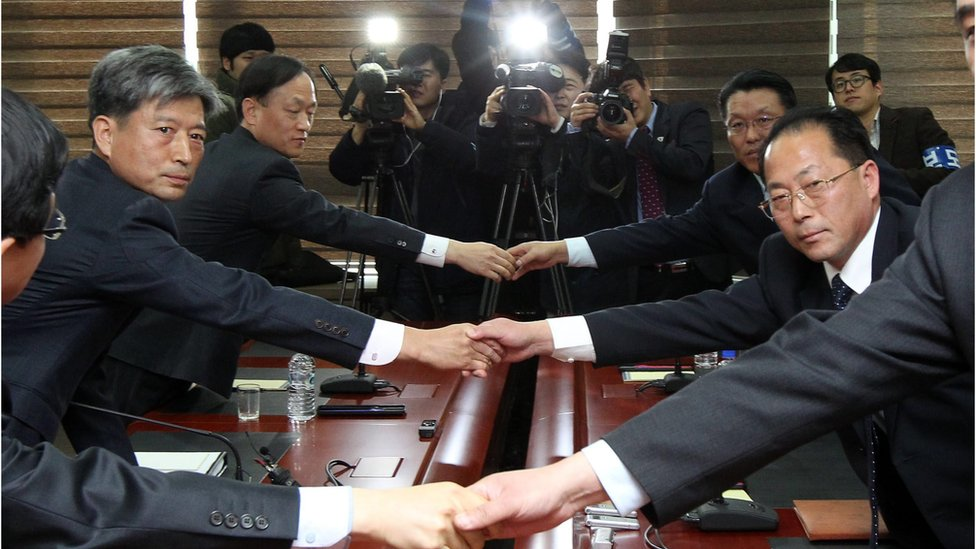 South and North Korean representatives to inter-Korean talks shake hands at the start of their meeting in the border city of Kaesong, North Korea, 11 December 2015