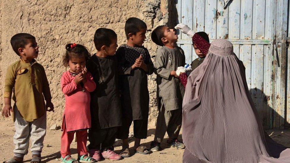 Una mujer vacuna niños en Afganistán