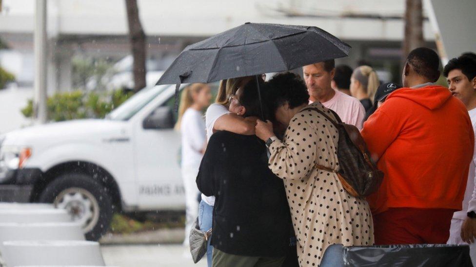 Varias personas esperan noticias en las inmediaciones del edificios derrumbado.