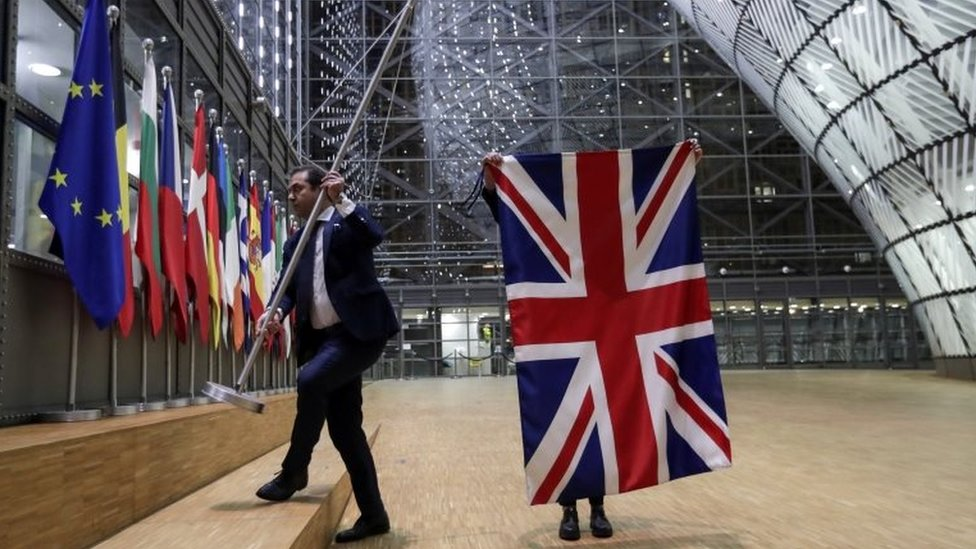 Officials remove the British flag at European Union Council in Brussels