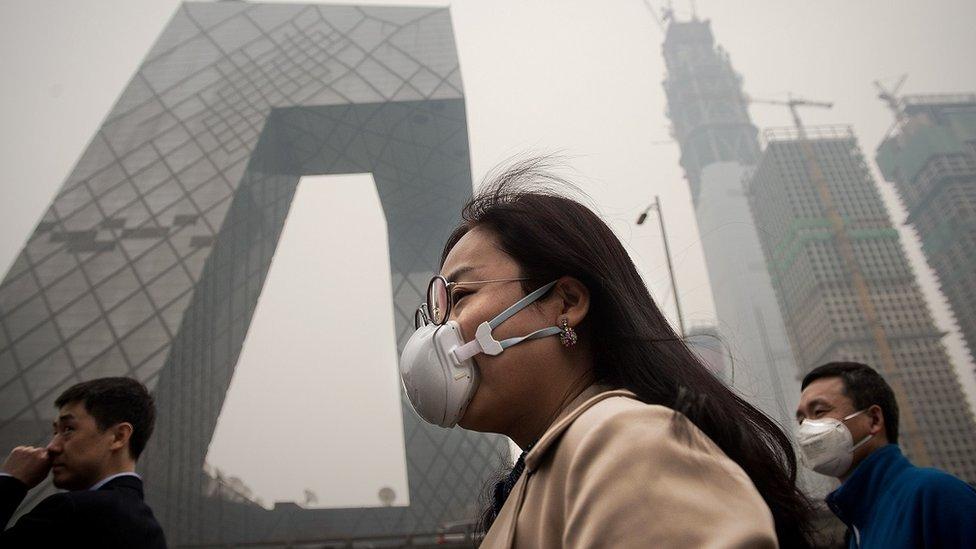 Una mujer usa una máscara en Pekín