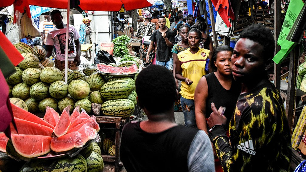 People walk at a market without social distancing April 15, 2020.