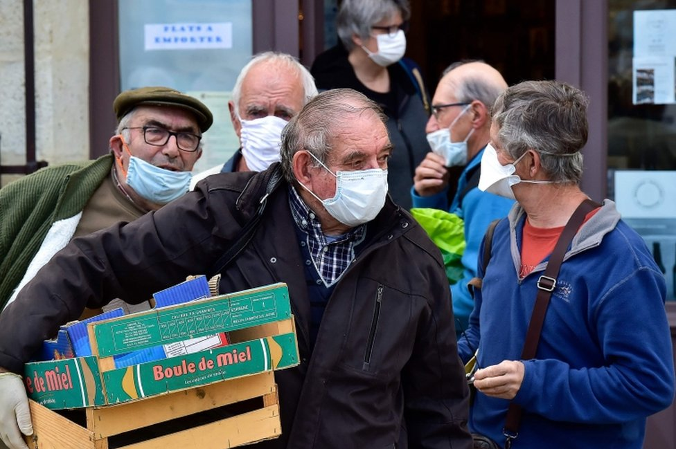 Wearing protective face masks, shoppers wait for their turn to enter the Cadillac market near the French city of Bordeaux on April 25, 2020