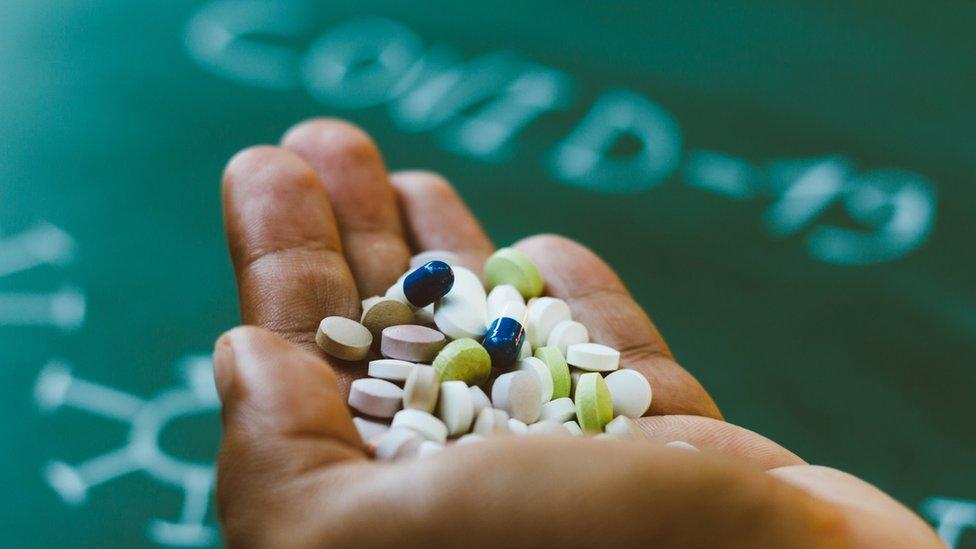 Mão segurando comprimidos com a palavra covid-19 desfocada ao fundo
