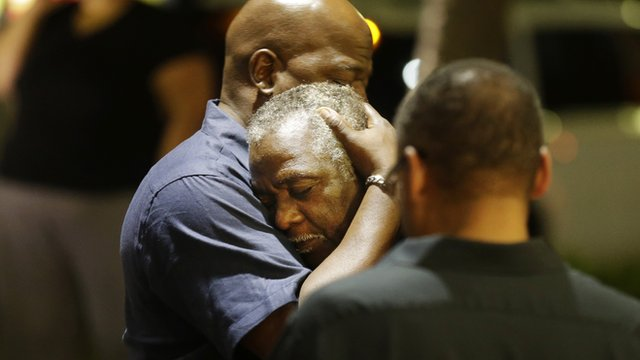 Men embrace near the site of a church shooting in South Carolina