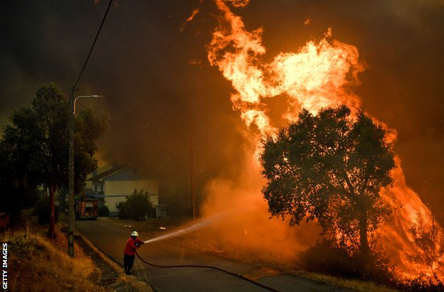 A firefighter tackles a wildfire close to the village of Pucarica in Abrantes on August 10, 2017