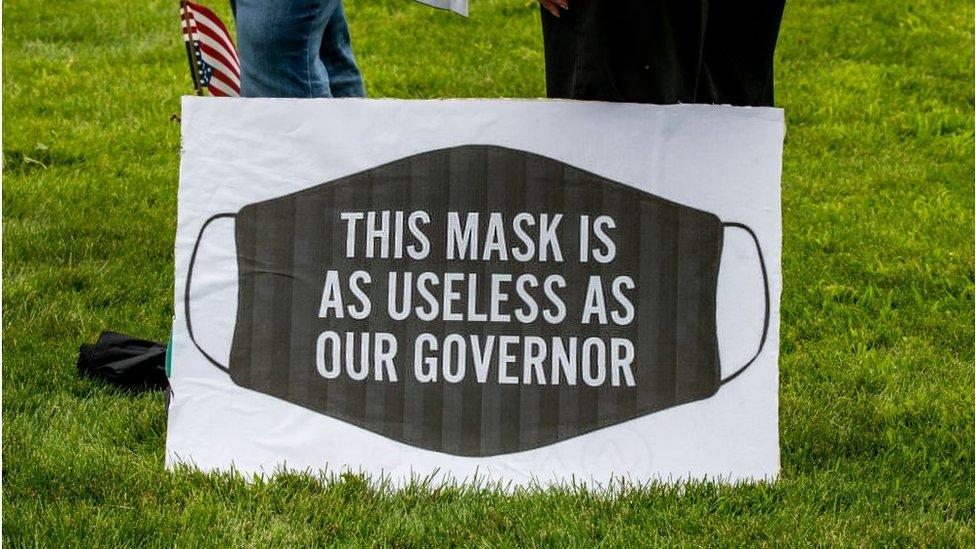 """Esta pancarta dice: """"Las mascarillas son tan inútiles como nuestro gobernador"""" y la llevaba una manifestante en una movilización en Minessota."""