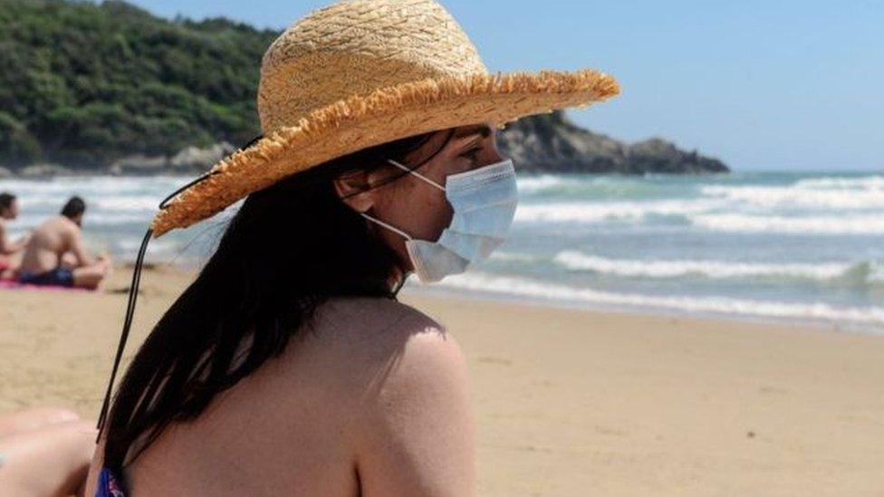 امرأة تجلس على الشاطئ مرتدية كمامة