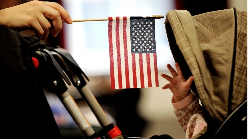 A baby reaches for an American flag held by her mother during naturalization ceremony at a federal building in New York, New York