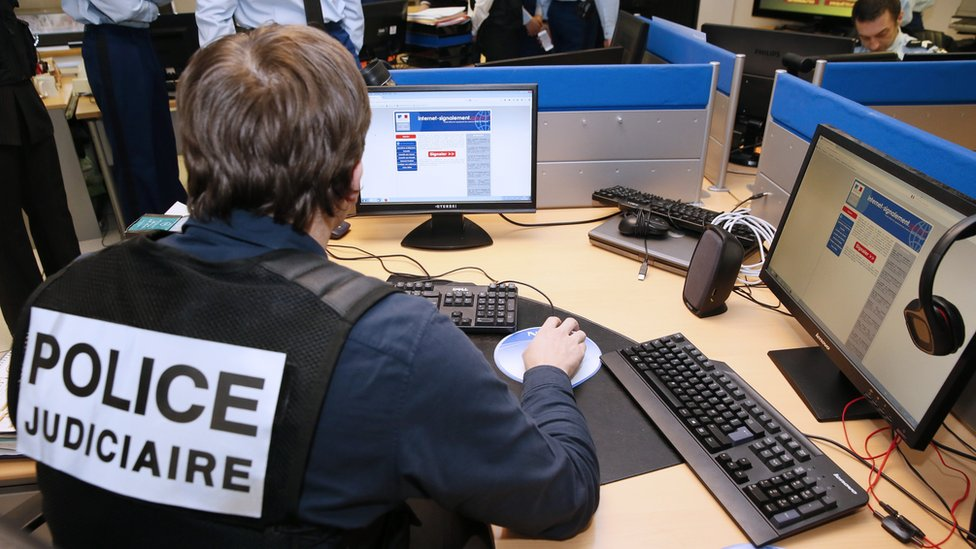 French police officers work at the headquarters of the Pharos reporting platform against cyber criminality