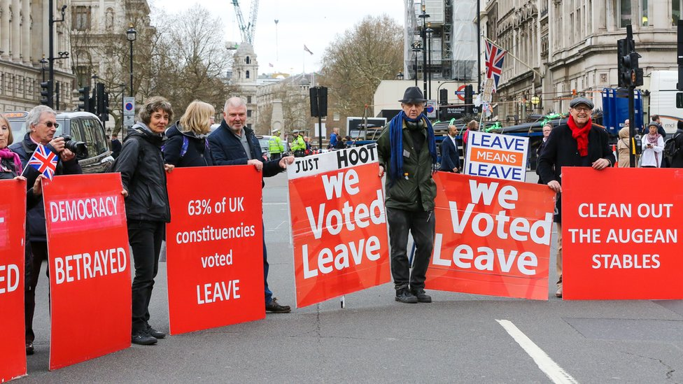 Pro-Brexit demonstrators with large colourful placards are seen protesting outside the Houses of Parliament