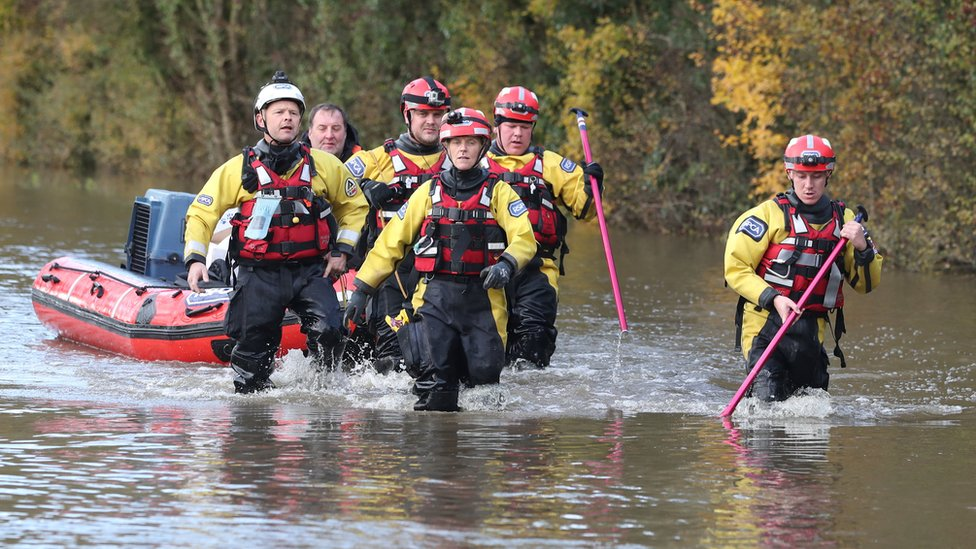 Rescuers pull a boat through floodwater in Fishlake, Doncaster