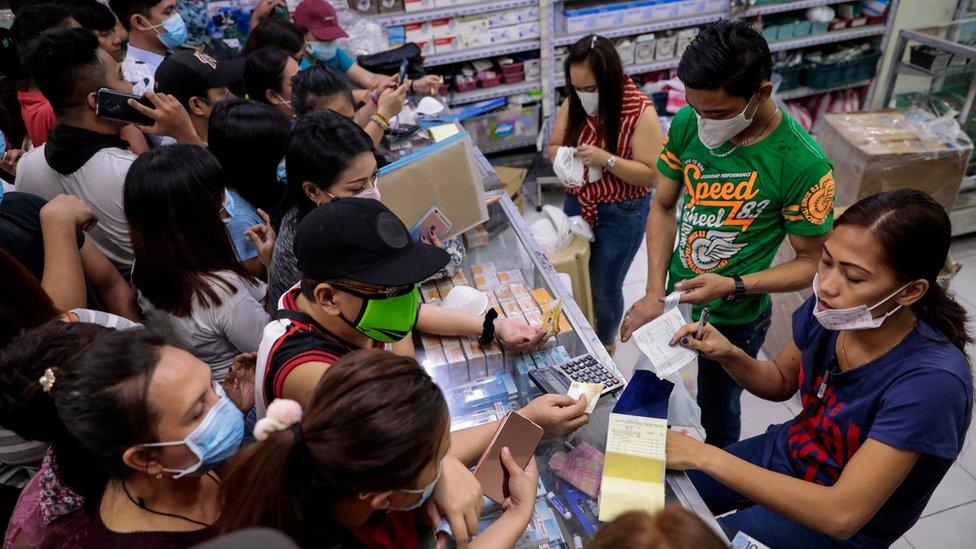Gente comprando mascarillas en una farmacia en Manila.