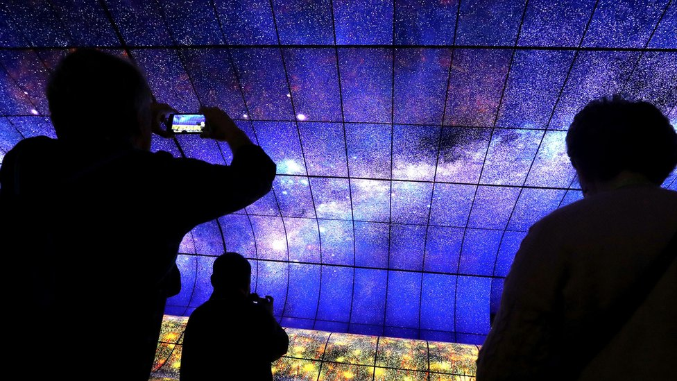 The LG screen wall is photographed by a smartphone user