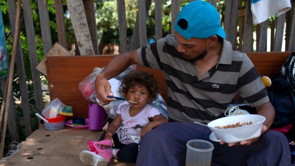 Migrante venezolano alimenta a su hija en la calle