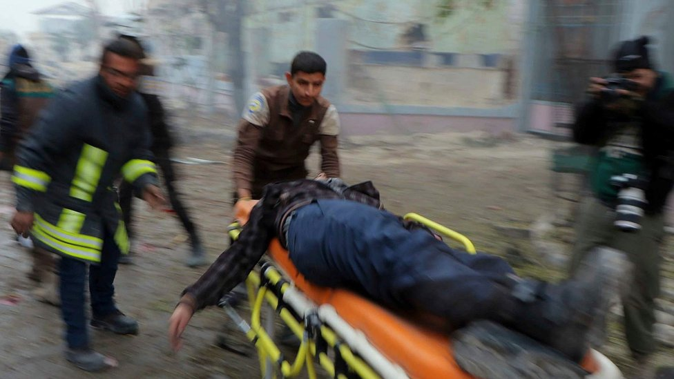 Photograph published by Syria Civil Defence showing man being taken away on a stretcher after a reported government artillery strike on the rebel-held Jubb al-Qubbeh district of Aleppo (30 November 2016)