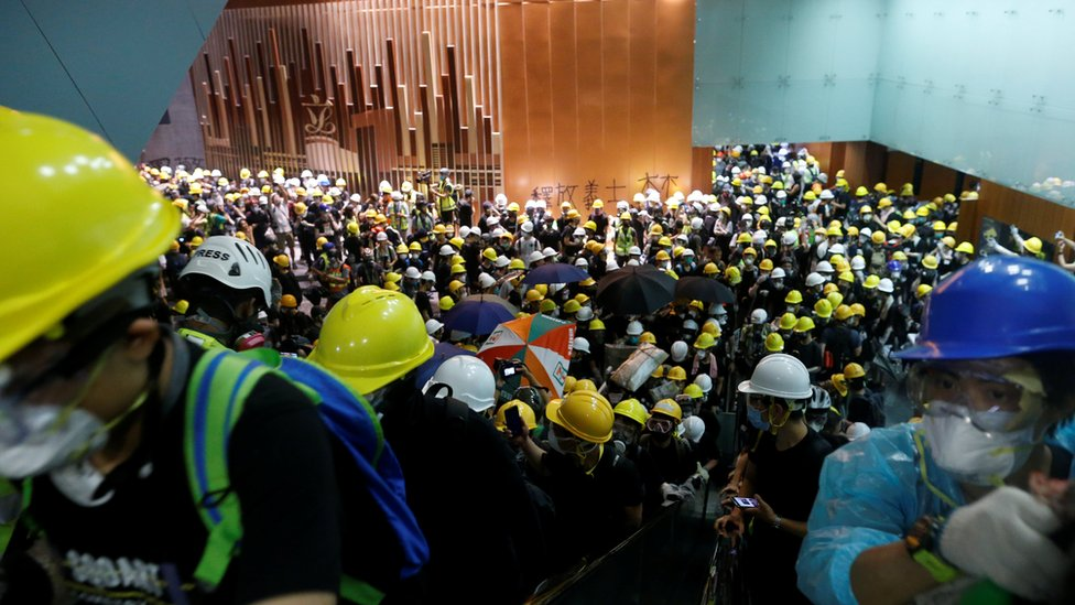 hundreds of people swarm the lobby of a legislative building, their yellow hard harts contrasting with the warm colours of the wooden relief carving against one wall