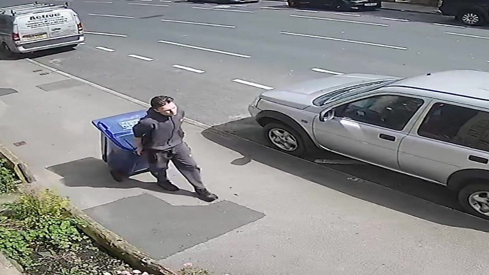 CCTV still released by police of Price pulling the wheelie bin