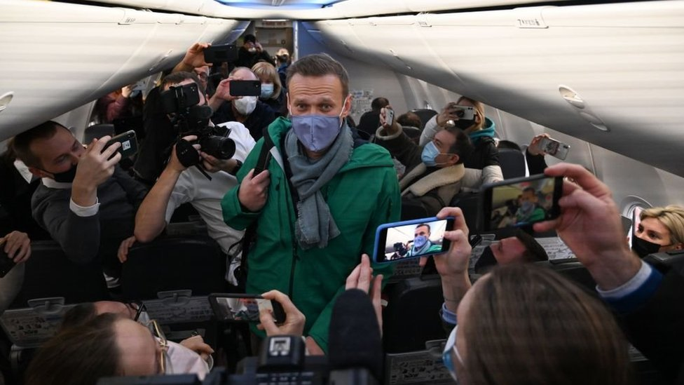 Russian opposition leader Alexei Navalny walks to take his seat in a Pobeda airlines plane heading to Moscow before take-off from Berlin Brandenburg Airport (BER) in Schoenefeld, southeast of Berlin, on January 17, 2021.