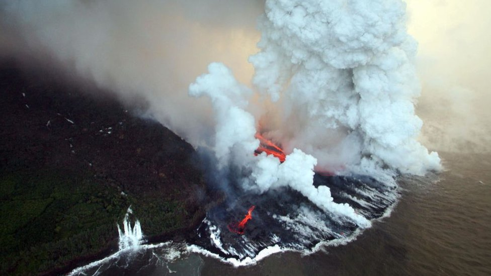 Aerial view taken 06 April 2007 near Tremblet in the French oversea island of La Reunion, of lava coming from the Piton de la Fournaise volcano burning vegetation and pouring into the Indian Ocean.