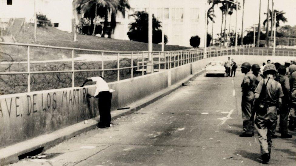 """Un hombre hace una pintada de """"Ave. de los Mártires"""" frente a la policía zoneíta."""