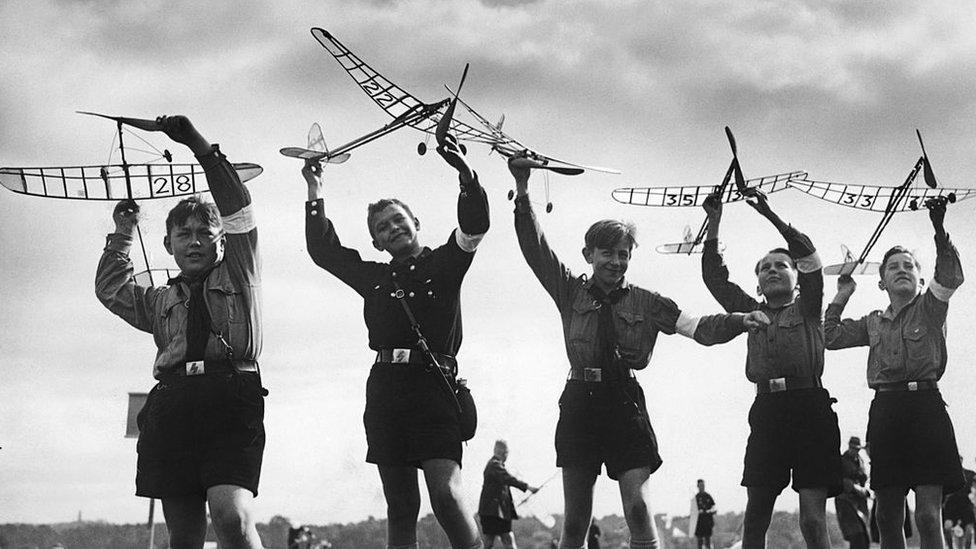 Niños alemanes con uniformes de la Juventud Hitleriana jugando con aviones de juguete.