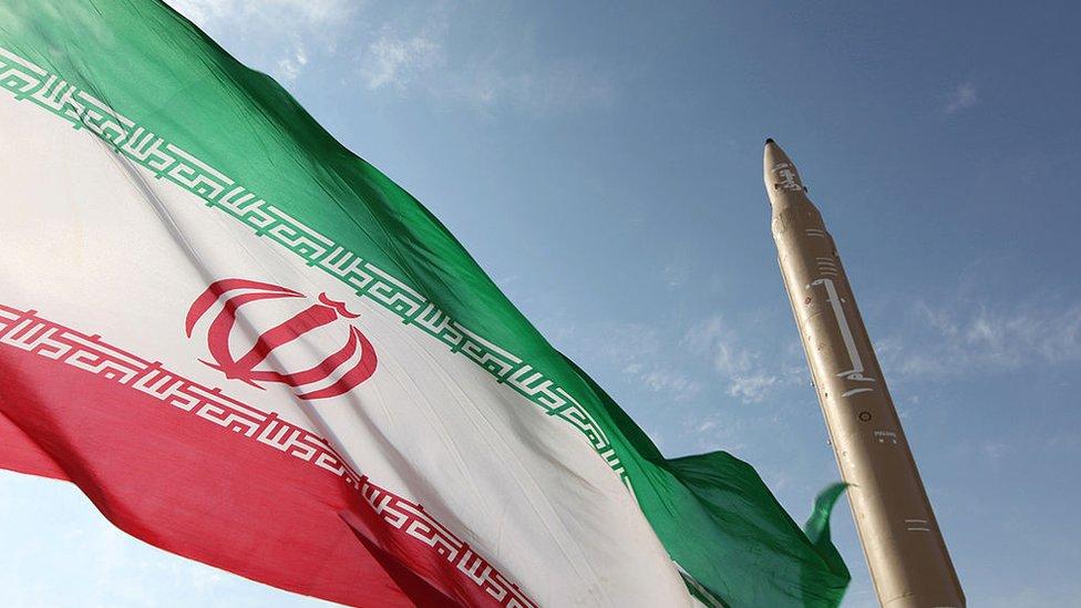 العلم الإيراني وإلى جواره صاروخ إيراني الصنع