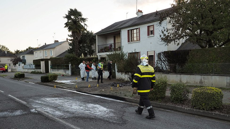 A fireman passes by near the site where an ULM crashed in Loches
