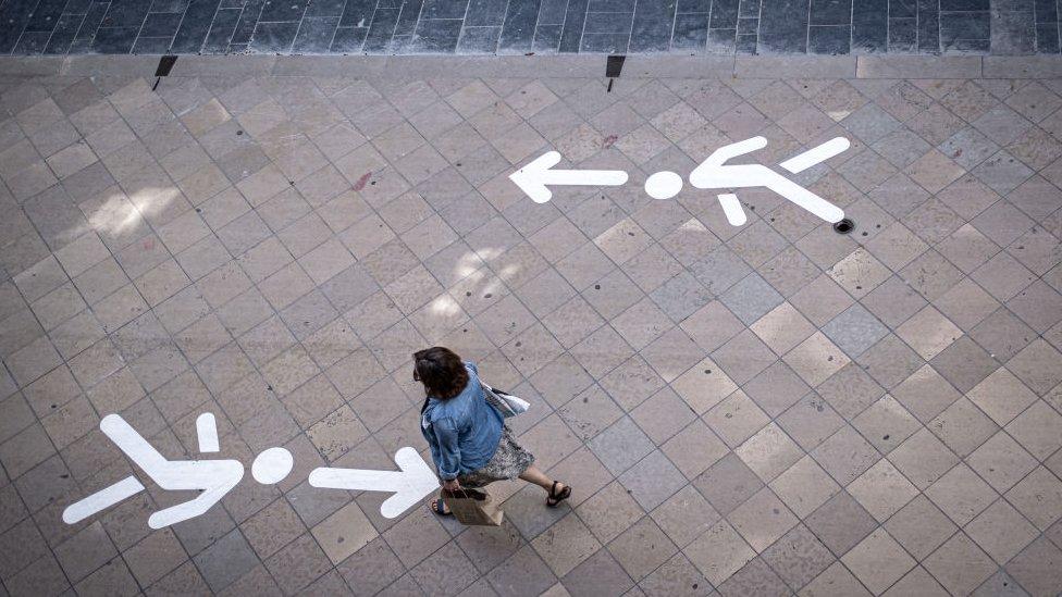 Acera señalizada en Burdeos, Francia, y una mujer caminando en contravía.