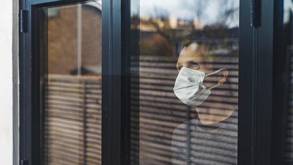 Homem com máscara dentro de casa