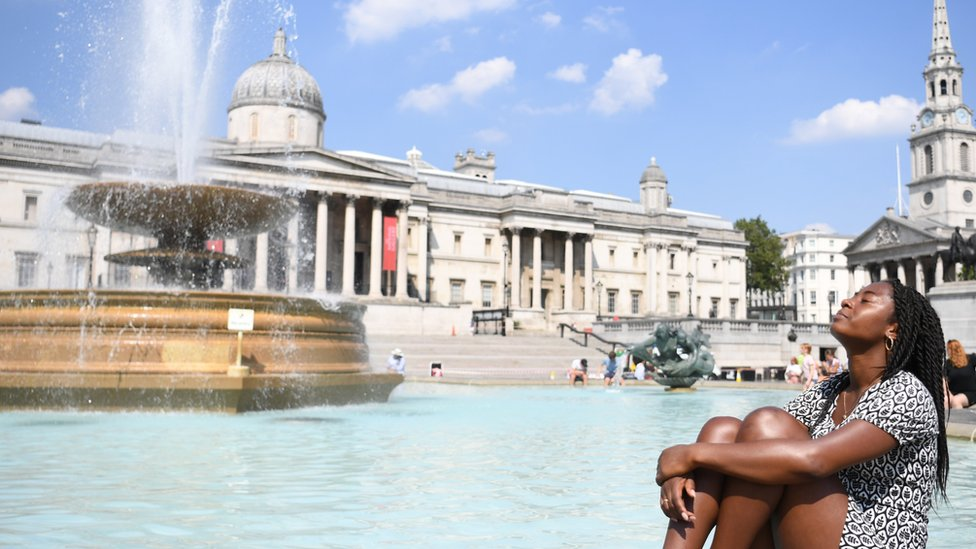 A woman relaxes in the sunshine at the fountains in Trafalgar Square in London, Britain 11 August 2020.