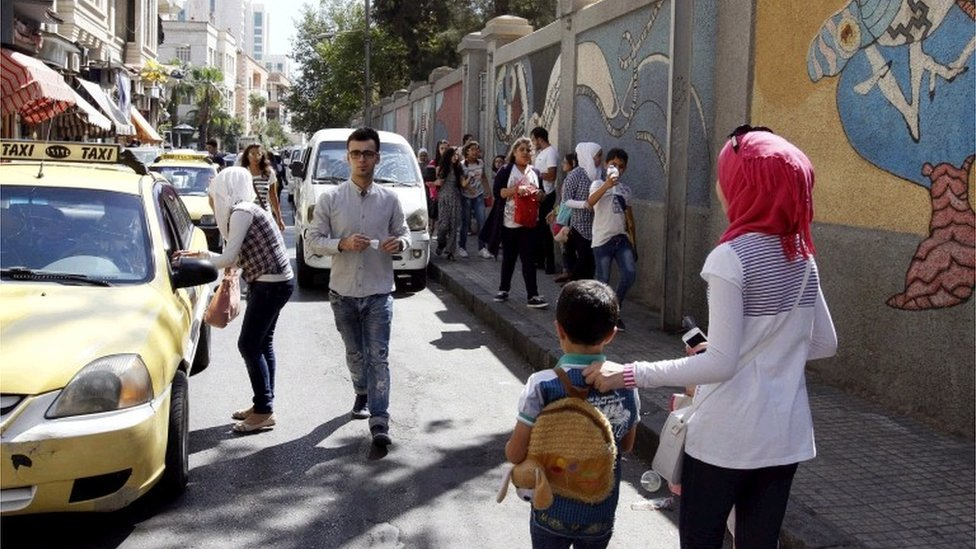 Syrian parents accompany their children as they come out of their school in Damascus, Syria, 18 September 2016. Some four million Syrian students started their school year in around 15,000 schools across the country.