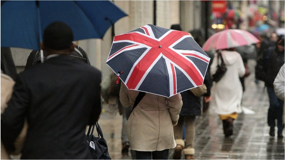 A shopper holds an umbrella decorated with the Union Jack flag