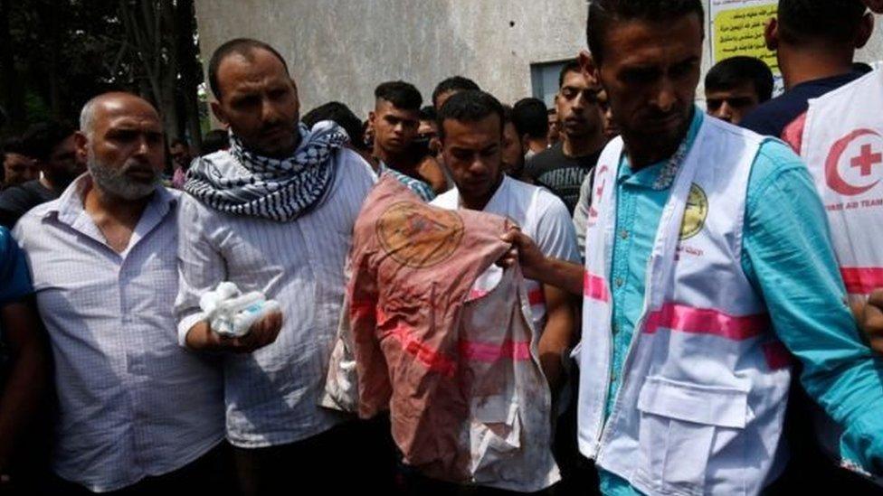 مشيعون حملوا سترة رزان الطبية الملطخة بالدماء أثناء تشييع جثمانها