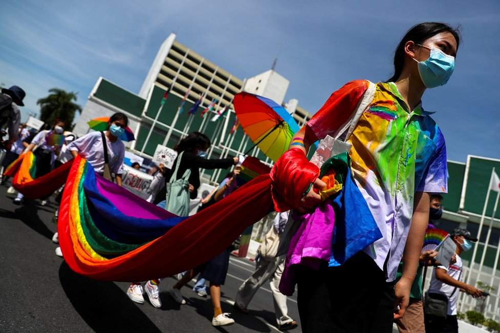 Members of a youth pride student group carry a long piece of rainbow-patterned fabric