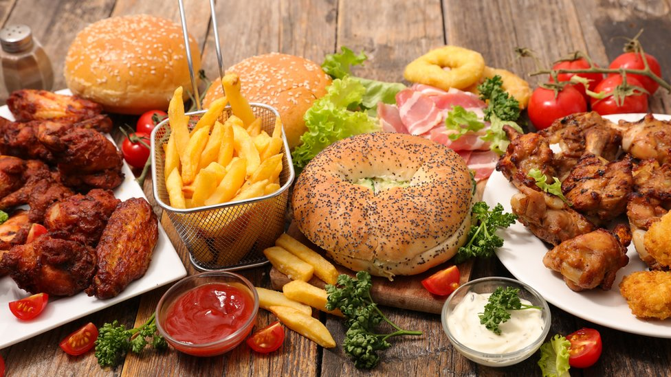 A variety of fast foods including burgers, chicken wings, chips etc.