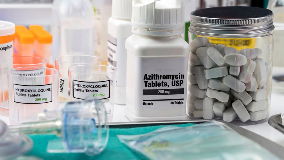 Frascos e pílulas de remédios, com rótulos mostrando 'hidroxicloroquina' e 'azitromicina'