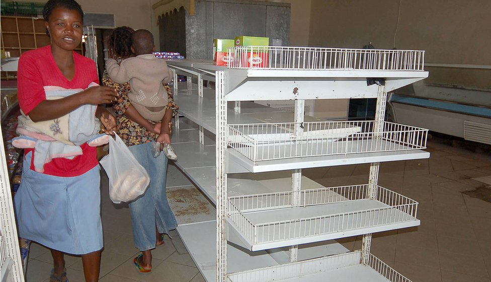 JULY 4th 2007: Zimbabwean shoppers walk past empty shelves in Mabvuku, Harare, Zimbabwe. Zimbabwe's government ordered shop owners to reduce prices on all goods by 50% which has resulted in an acute shortage of most basic commodities. President Robert Mugabe has accused businesses of profiteering and working in cahoots with the country's enemies to incite people to revolt against his government.