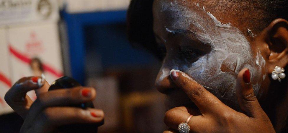 Una esteticista que trabaja en Nairobi hace una demostración de cómo aplicar la crema blanqueadora