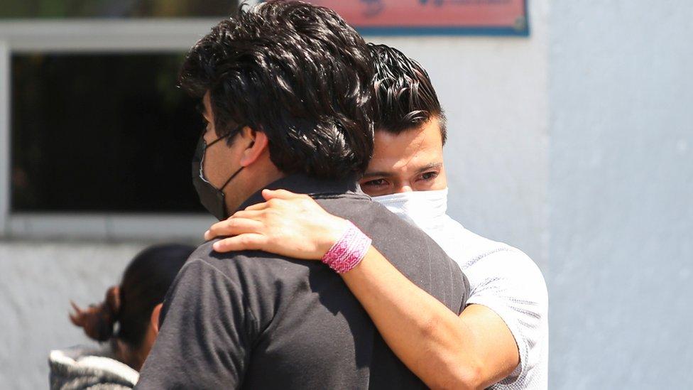 Un hombre y una mujer abrazados esperan noticias de sus familiares
