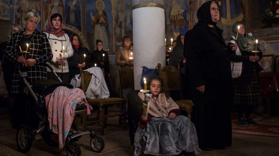 Pravoslavni vernici drže sveće tokom ponoćne uskršnje liturgije u manastiru Sukovo u istočnoj Srbiji