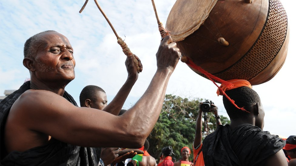 A man plays the drum as he gathers with other Ghanaian mourners to watch the casket carrying the remains of late Ghanaian President John Atta Mills being driven through the streets of Accra, from the State House parliamentary complex, where it had lain in state since August 8, 2012, to Independence Square, for the funeral service